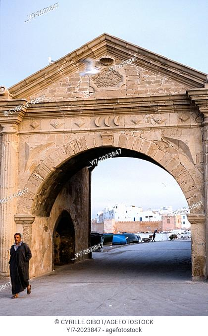 Man in Djellaba Passing Old City Gate in Essaouira, Morocco. Essaouira was laid out by a French architect who had been profoundly influenced by the work of...