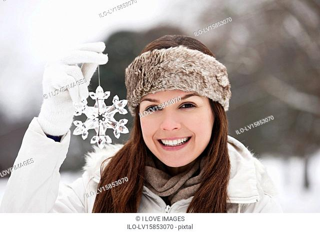A young woman holding a snowflake decoration