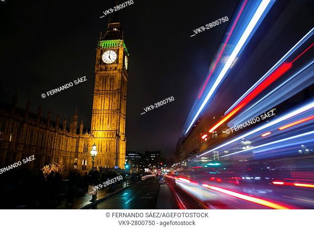 A bus passing in the road to Big Ben at night, London