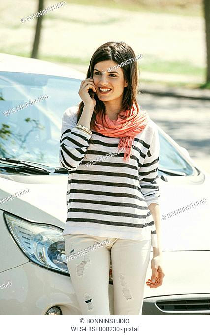 Spain, Barcelona, Young woman at car on cell phone