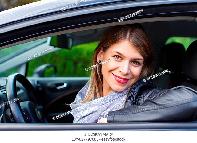 Portrait of a beautiful young woman in her new car
