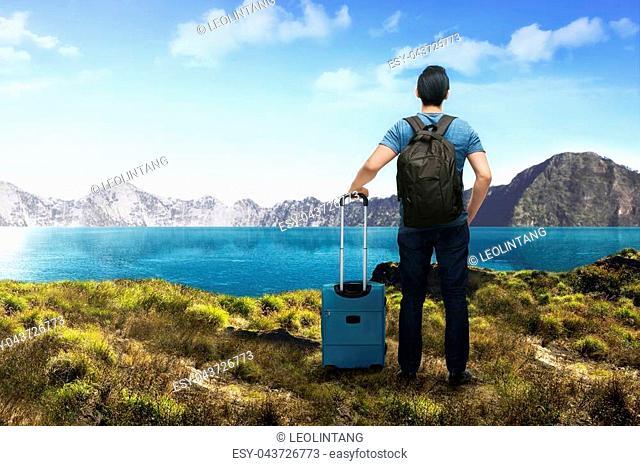 Back view of asian traveler man with suitcase enjoying lake view at mountain