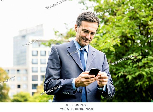 Businessman using cell phone in city park
