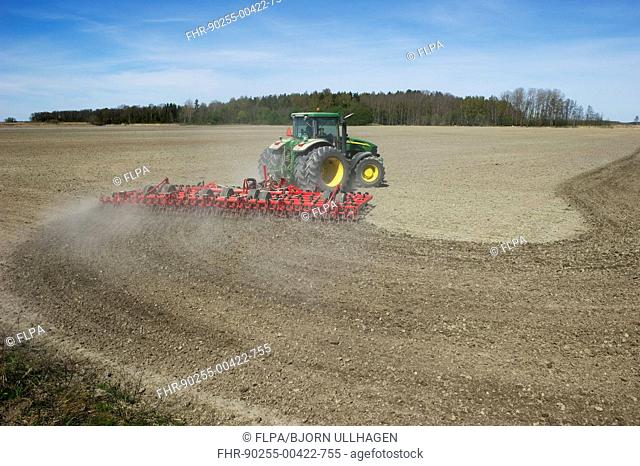 John Deere 7720 tractor with Vaderstad NZ-Aggressive-800 harrows, harrowing arable field, Sweden, may