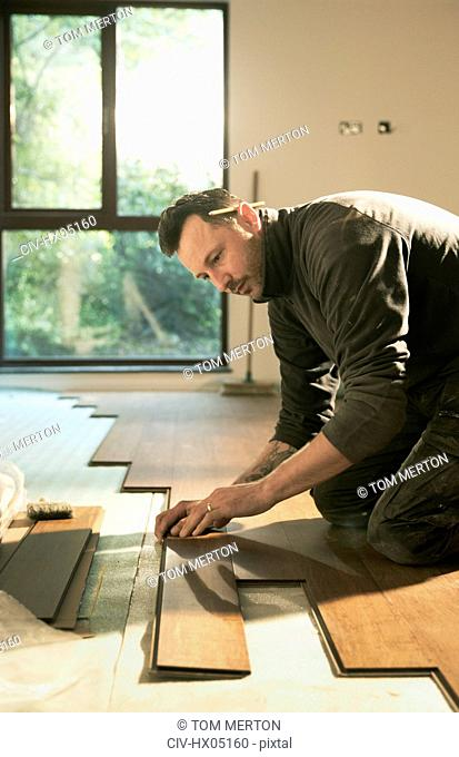 Focused construction worker laying hardwood flooring in house