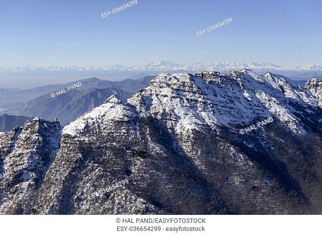 aerial shot, from a small plane, of Resegone peak eastern side covered with the first winter snow, shot on a bright early winter day near Bergamo, Orobie