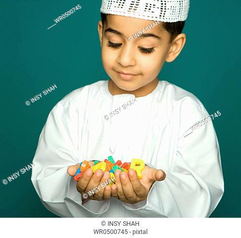 Boy 8-9 holding colorful alphabets, smiling, portrait