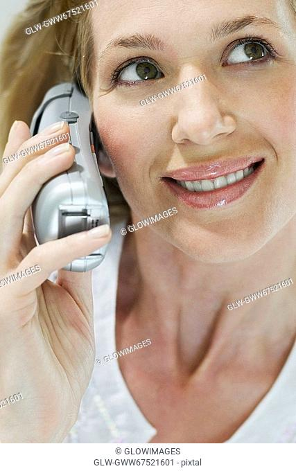 Close-up of a young woman talking on a cordless phone