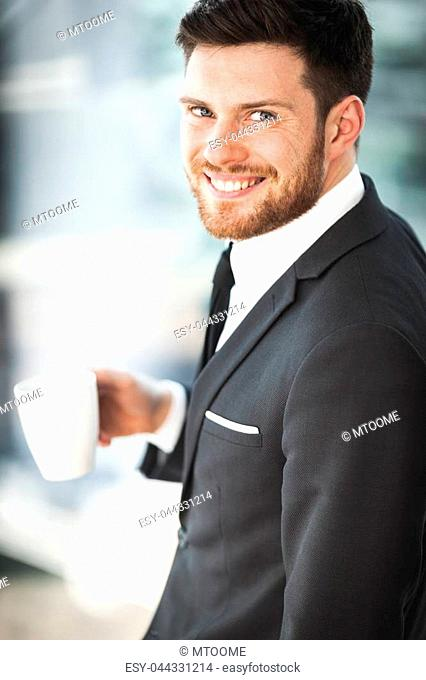 Young businessman at the office standing near window and drinking coffee