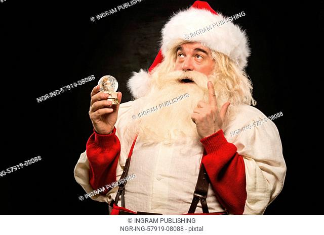 Santa Claus holding snow globe against dark background