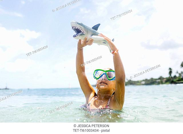 Girl (6-7) playing with shark toy in sea