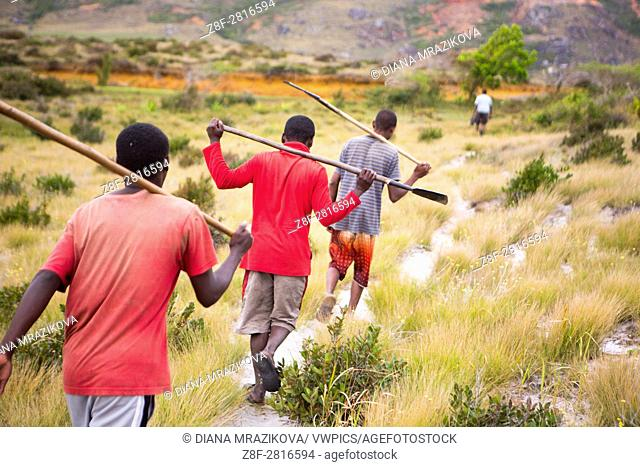 Malagasy men commuting for work - walking on a cross-country trail carrying their work tools
