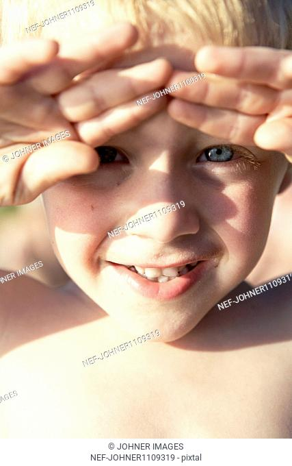 Portrait of boy touching forehead with hands