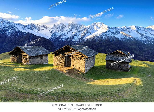 Meadows and alpine huts framed by snowy peaks at dawn Tombal Soglio Bregaglia Valley canton of Graubünden Switzerland Europe