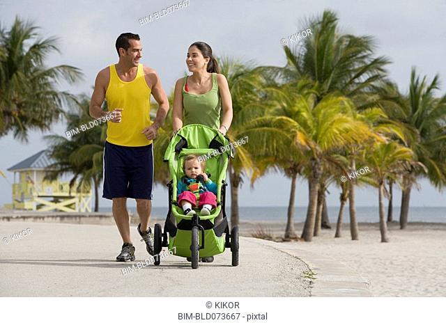 Hispanic couple pushing baby in jogging stroller