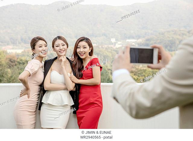 Three young smiling women posing for photos at party on rooftop