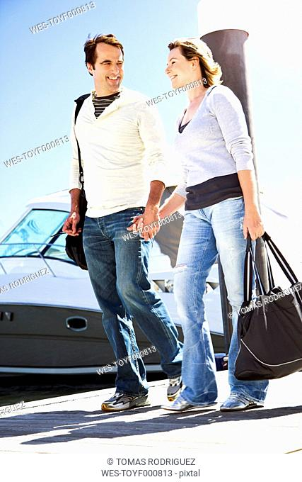Mature couple walking hand in hand on jetty