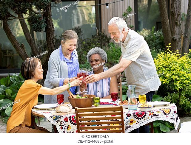 Active senior friends enjoying rose wine and lunch at patio table