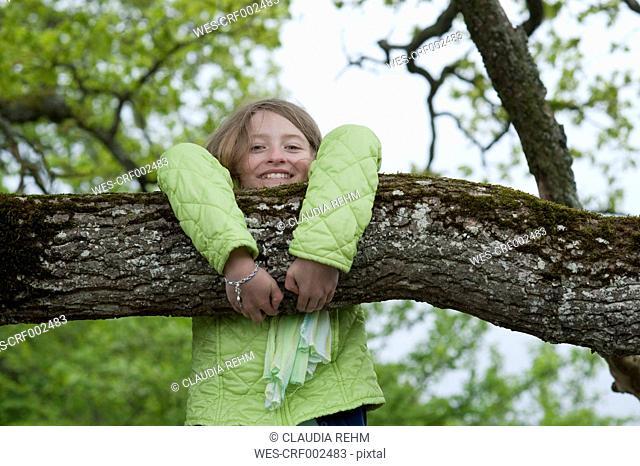 Germany, Bavaria, girl climbing on a tree