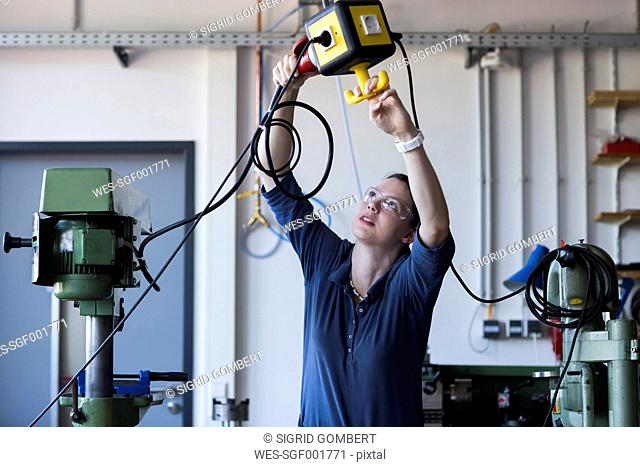 Young woman with safety goggles installing a three-phase plug