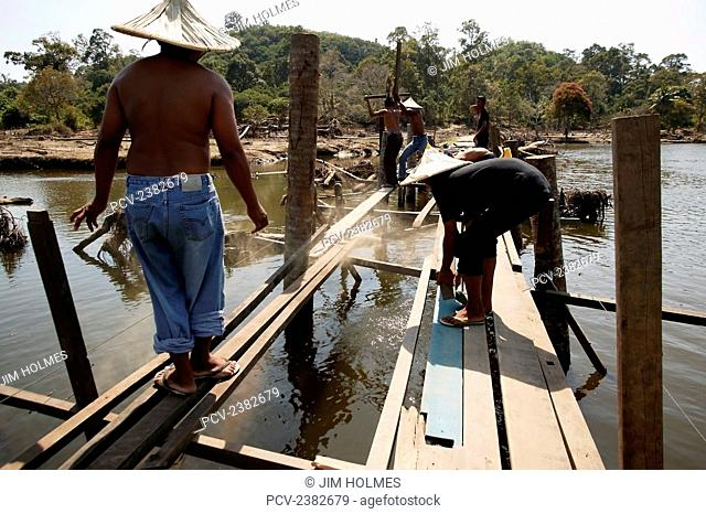 Villagers worked as a team to reconstruct a bridge after the Indian Ocean earthquake and tsunami, near Lamno; Aceh Province, Indonesia