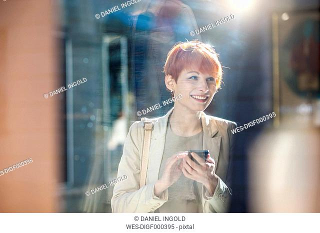 Smiling young woman holding cell phone looking at shop window