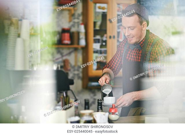 Young barista pouring coffee in cup