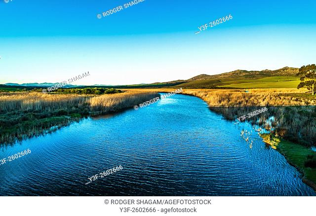 Calm with a slight breeze causing a light ripple on the river water. Bot River, South Africa