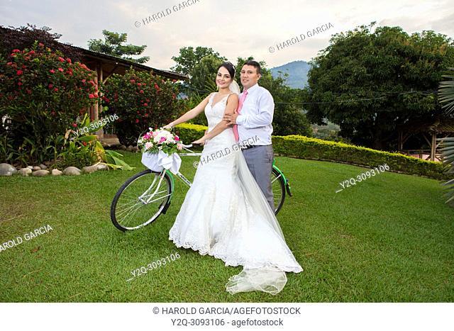 Wedding couple posing with a bike