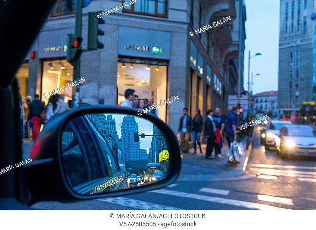 Aspect of the city at night through a car's rear view mirror. Gran Via street, Madrid, Spain