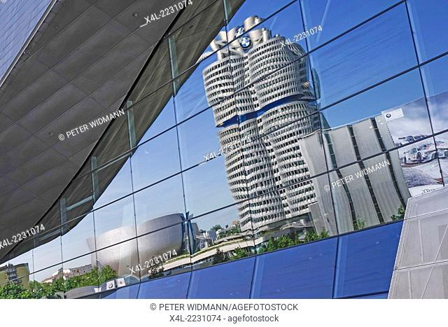 BMW headquarters is reflected in the glass facade of the BMW Welt, Munich, Bavaria, Germany, Europe