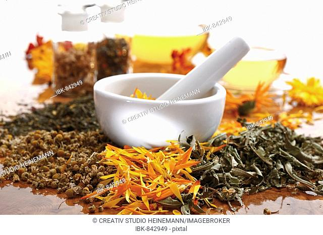 Mortar and pestle with chamomile, marigold, and vervain or verbena
