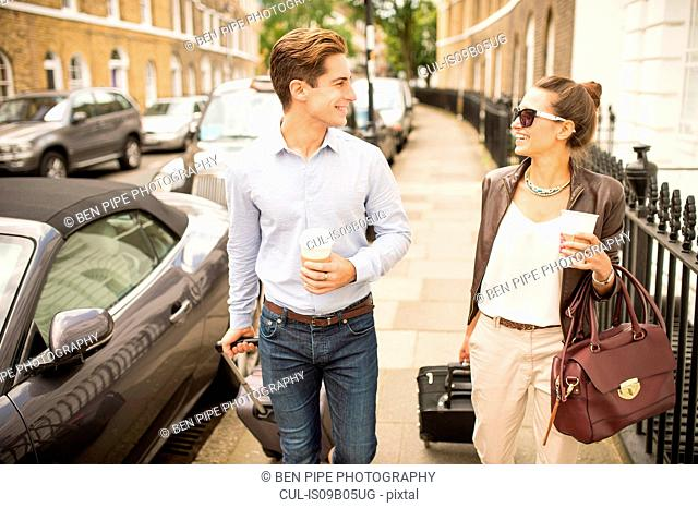 Businessman and woman walking and talking with wheeled suitcases, London, UK
