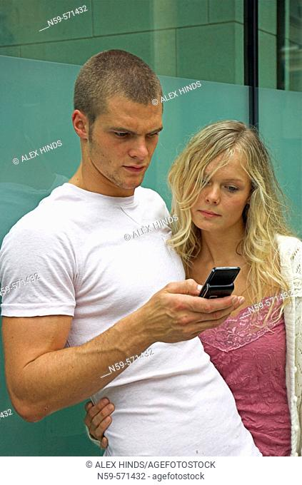 Attractive young urban couple, looking at messages on mobile phone