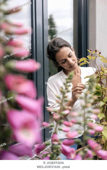 Woman caring for plant on balcony