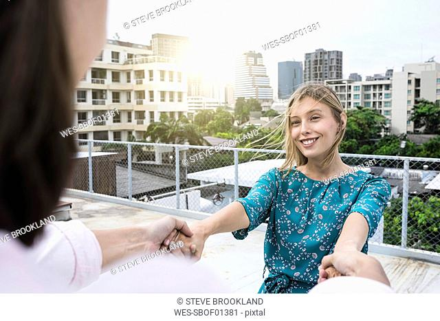 Young woman holding hands with boyfriend on rooftop