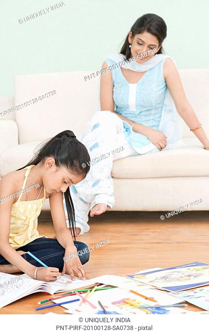 Woman looking at her daughter sitting on the floor and drawing
