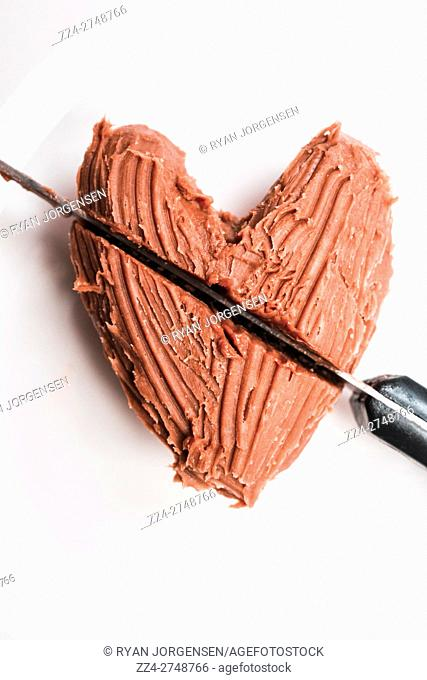 Closeup of knife cutting heart shape chocolate dessert on white plate. Eat your heart out
