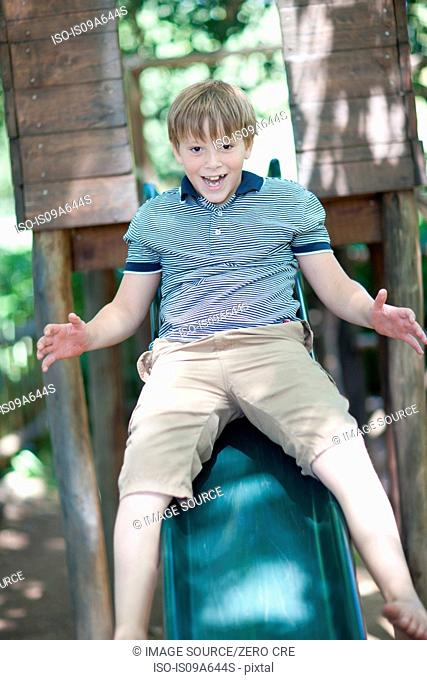 Boy playing on slide outdoors