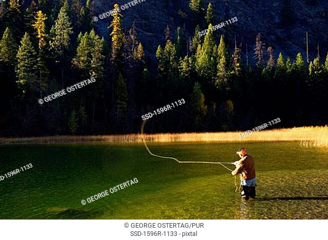 Man fly-fishing in a pond, Sherman Pass Scenic Byway, Colville National Forest, Washington State, USA