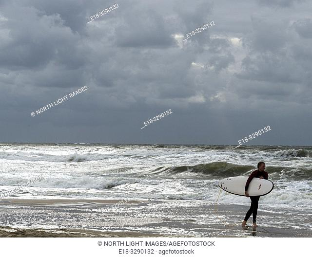 Netherlands, Bergen. A kite surfer carries her surfboard away from the turbulent waters of the North Sea