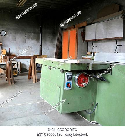 old big machine to cut the wooden planks in an abandoned carpentry