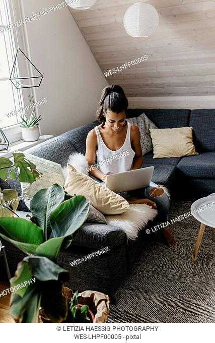 Smiling young woman sitting on the couch at home using laptop