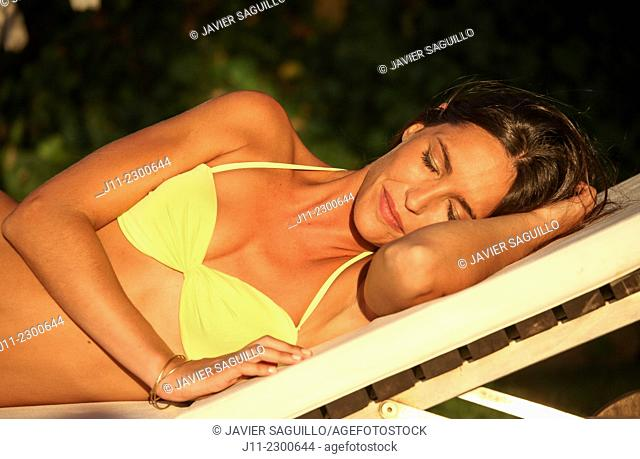 Woman lying down on sunlounger