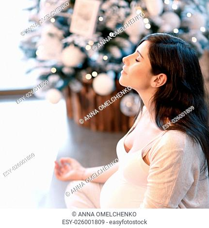 Healthy pregnant woman doing yoga exercise at home in Christmastime, with closed eyes sitting in lotus pose and meditating, inner peace and harmony
