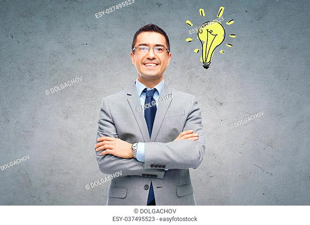 business, people, inspiration and idea concept - happy smiling businessman in eyeglasses and suit over gray concrete wall background