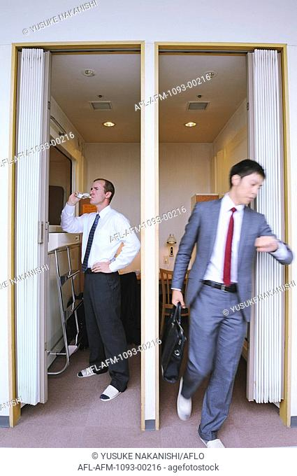 Businesspeople drinking juice and checking time