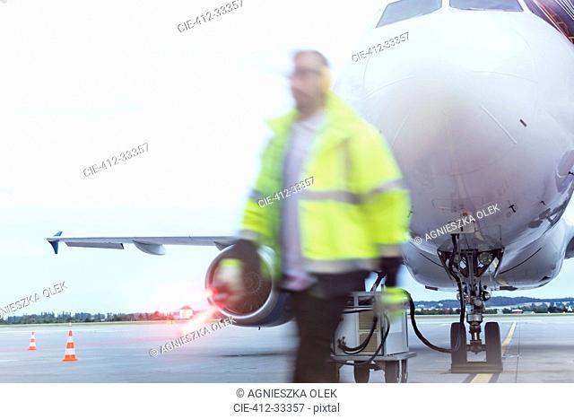 Air traffic controller walking past airplane on tarmac