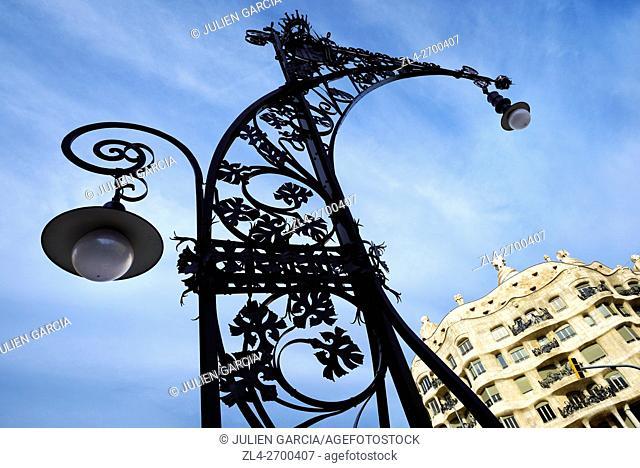 Spain, Catalonia, Barcelona, a Modernist streetlight on Passeig de Gracia by Pere Falques (1906) and La Pedrera (or Casa Mila
