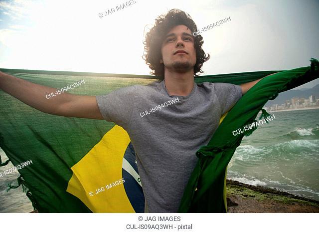 Young man holding up Brazilian flag, Ipanema beach, Rio De Janeiro, Brazil